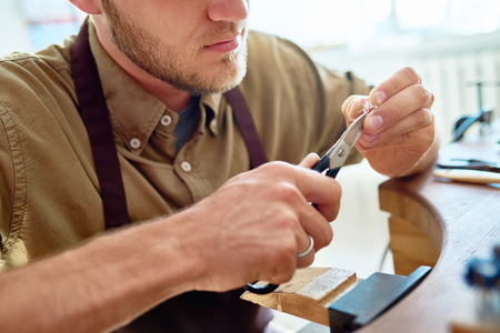 Closeup  portrait of jeweler making flower ring in workshop, forming silver wire with tongs Stock Photo