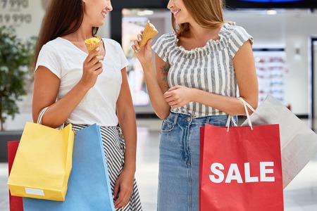 Medio sectieportret van twee mooie meisjes die in wandelgalerij winkelen, die document zakken houden en roomijs eten