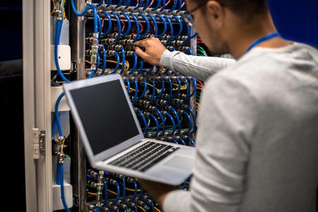 블레이드 서버 케이블을 연결하고 노트북에서 데이터를 확인하는 슈퍼 컴퓨터로 작업하는 젊은이의 초상화를 다시 본다.