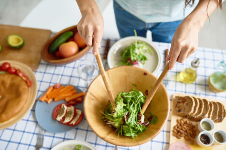Closeup of female hands mixing green salad in wooden bowl at table with wholesome food while preparing family dinner