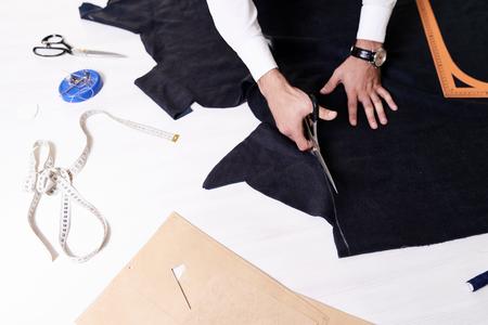 Hoogste mening van kleermakerslijst met verschillende hulpmiddelen, mannelijke handen die stof op het snijden die patroon voor kleren maken