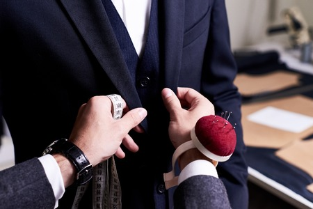 Closeup of tailor fitting bespoke suit to model, hands with tape measure and pin cushion fixing jacket on male model