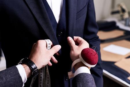 Primer plano del traje a medida del modelo, las manos con cinta métrica y la chaqueta de fijación con alfileres en el modelo masculino