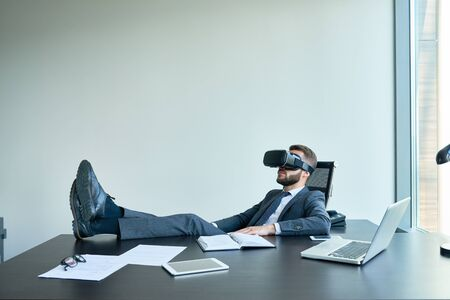 Portrait of handsome modern businessman wearing VR glasses relaxing at desk in office with feet on table