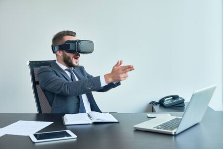 Portrait of handsome modern businessman using VR glasses playing shooter game sitting at desk in office