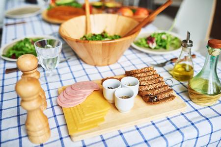 Hoher Winkel des köstlichen gesunden Lebensmittels auf rustikaler Tabelle über blauer Tischdecke des Ginghams: Sandwiches und grüner Salat in der hölzernen Schüssel Standard-Bild - 88489694
