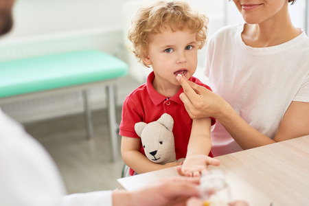 Portrait of cute curly-haired little boy taking pills in doctors office and looking at camera holding teddy bear toy