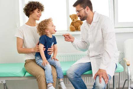 母親の膝の上に座って、医師のオフィスで検診のために口を開く愛らしい少年の肖像画