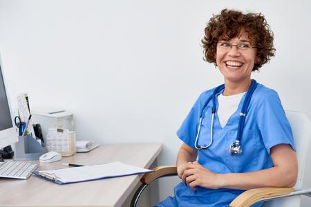 친절한 여성 의사의 사무실에서 책상에 앉아 행복하게 웃으면 서, 공간 복사의 초상화 스톡 콘텐츠