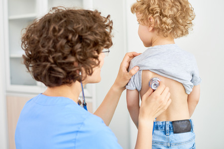 Portrait of female doctor listening to childs breathing from the back using stethoscope to check for symptoms of bronchitis or pneumonia