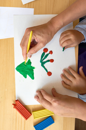 Above view closeup of parent making Christmas picture with child using plasticine