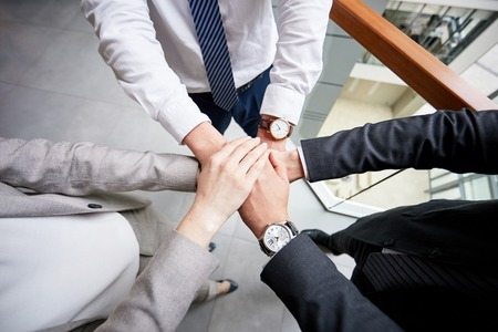 Close-up shot of ambitious team of managers joining hands together after successful completion of negotiations with business partners, interior of office lobby on background