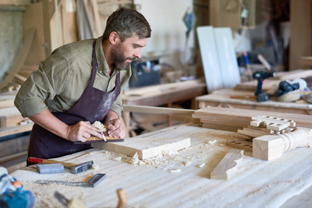 Bearded Carpenter Working with Wood in Shop