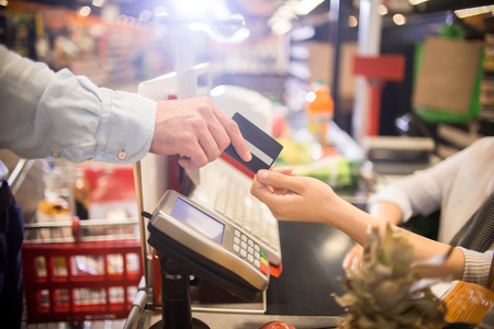 Side view close up of unrecognizable customer handing credit card to cashier paying via bank terminal at grocery store Foto de archivo