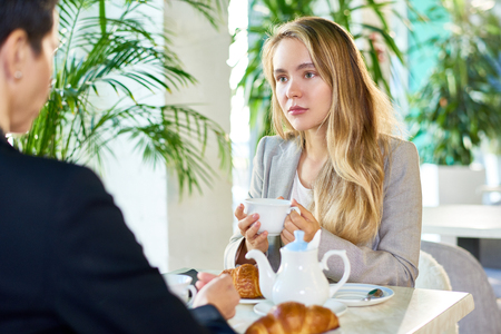 Pretty Young Businesswoman Drinking Coffee during Meeting in Cafe