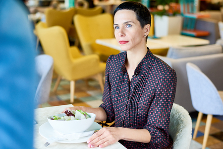Elegant Woman at Cafe Table Stock Photo