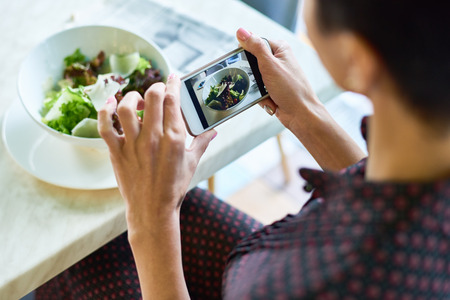 Young Woman Taking Photo of Salad in Cafe Banco de Imagens