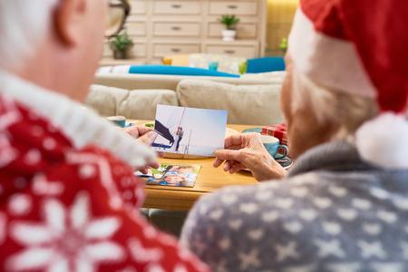 クリスマスに家族の写真を見てシニア カップル 写真素材