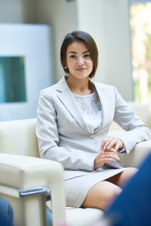 Young Businesswoman Listening to Partners in Meeting Stock Photo