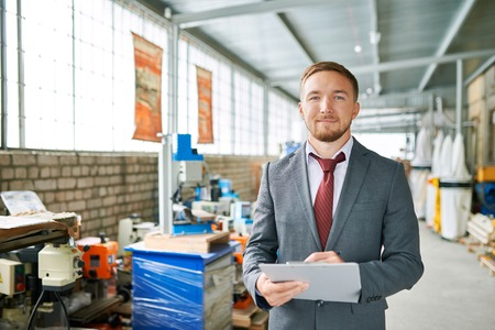 Successful Salesman Posing in Machine Shop