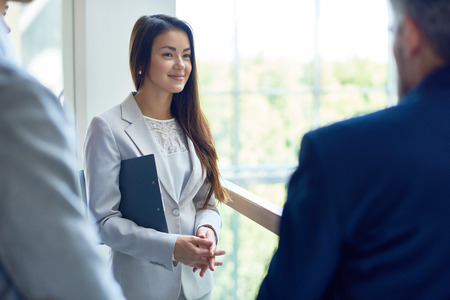 Young Businesswoman Talking with Colleagues Stock Photo