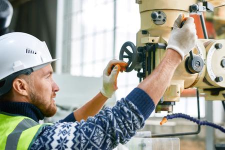 Fabrieksarbeider met behulp van machine-eenheden Stockfoto