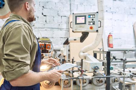 Werknemer met behulp van moderne machine in de fabriek Stockfoto