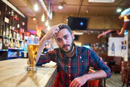 Young Man Sitting at Bar Counter
