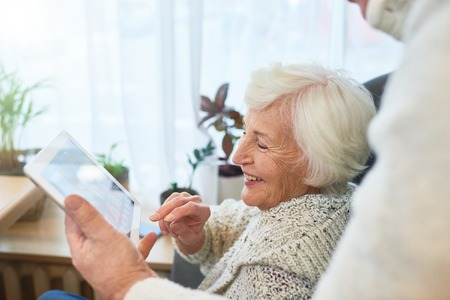 Laughing Elderly Lady que usa la tableta Foto de archivo - 91627753