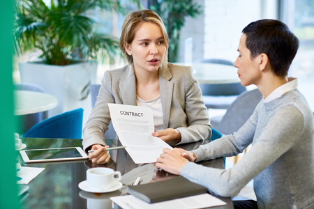 Female Business Partners Discussing Contract Stock Photo