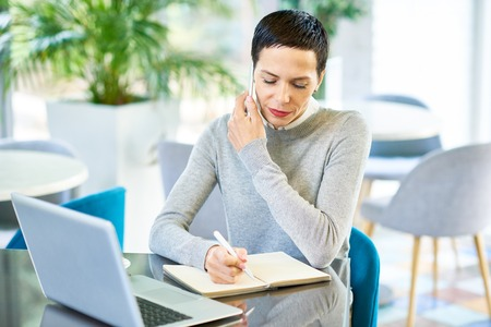 Businesswoman Speaking by Phone with Client Stock Photo