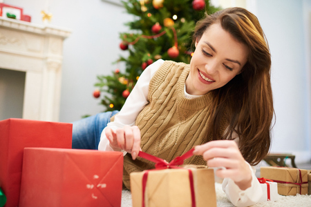 Curious Woman Unwrapping Christmas Gift Box