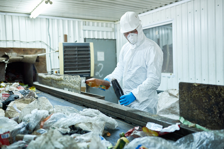 Worker Sorting Trash on Waste Processing Plan Stock Photo