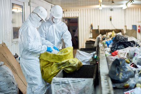 Workers Sorting Recyclable Materials at Waste Processing Plant