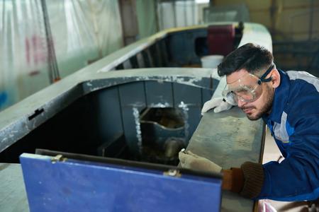 ワークショップでボートを修理するハンサムな男