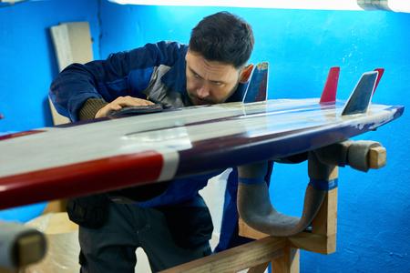 Handsome Man Polishing Custom Surfing Board