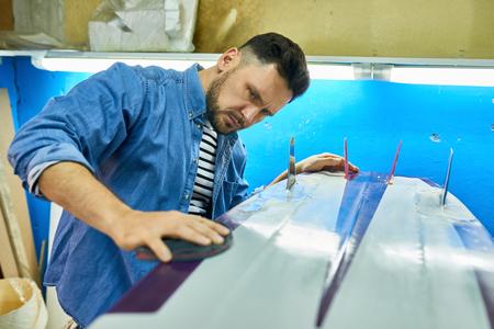 Handsome Man Polishing handmade Surfing Board