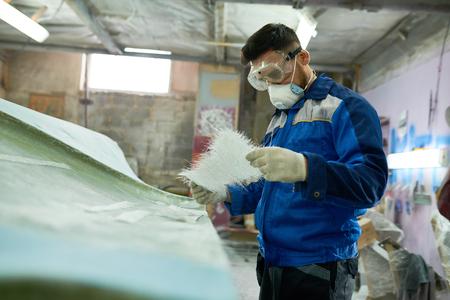 Worker Repairing Boat in Workshop 版權商用圖片