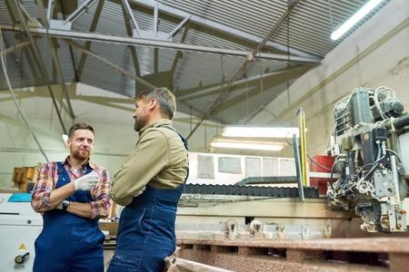 Twee fabrieksarbeiders chatten in werkplaats