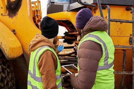 Mechanics Inspecting Truck Outdoors