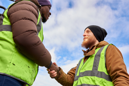 Workers Shaking Hands Outdoors