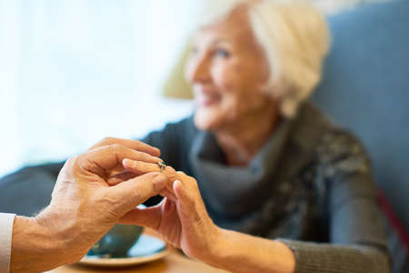 Close-up shot of elderly fiance putting engagement ring on finger of pretty woman while sitting at restaurant, focus on foreground Stock Photo