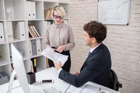 Portrait of young blonde businesswoman showing contract to partner while discussing deal in modern office