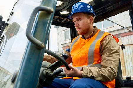Bearded Worker Driving Lift Truck Фото со стока