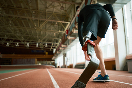 Motivational image of young amputee athlete on start position on running track in modern indoor stadium, focus on artificial foot, copy space Archivio Fotografico