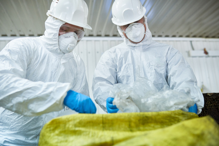 Portrait of two workers wearing biohazard suits sorting recyclable plastic and cardboard on conveyor belt at waste processing plant Stock Photo