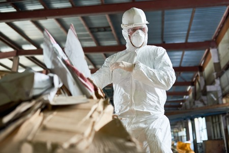 Low angle portrait of factory worker wearing biohazard suit sorting reusable cardboard on waste processing plant, copy space Banco de Imagens