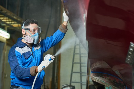 Worker Spray Painting Boats in Workshop