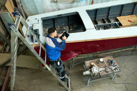 税関ワークショップでボートを修理する男
