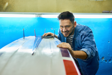 Excited Man Polishing Custom Surfing Board